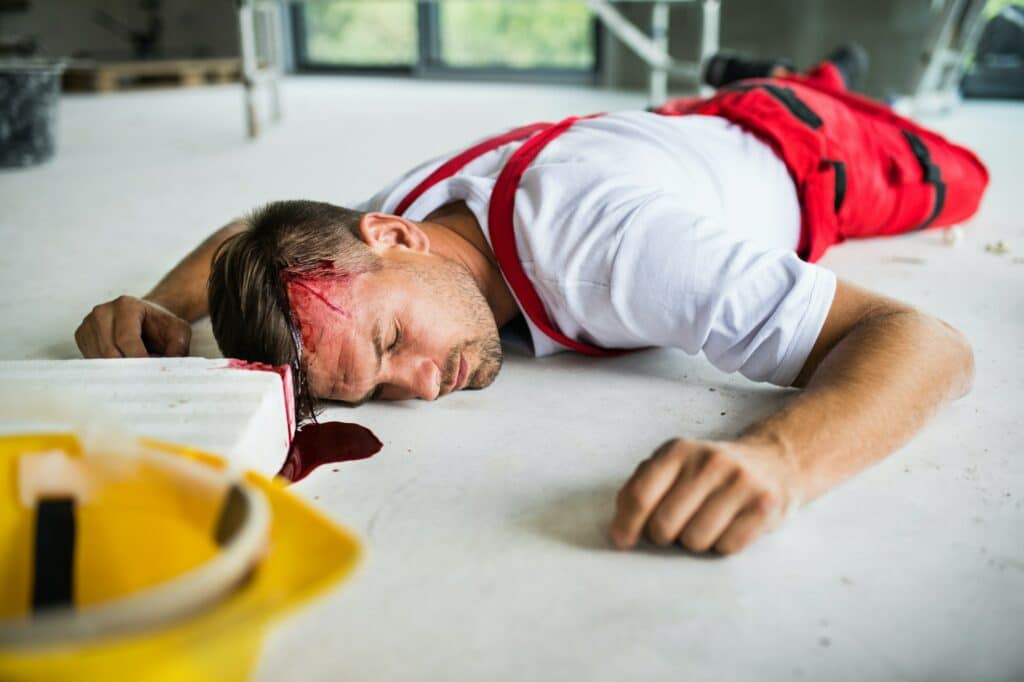 An unconscious man worker lying on the floor after accident on the construction site.